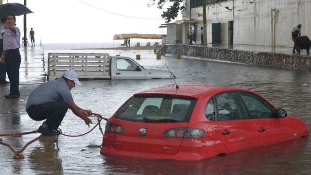 Ein Mann versucht ein Sicherungsseil an einem Auto im Wasser anzubringen.