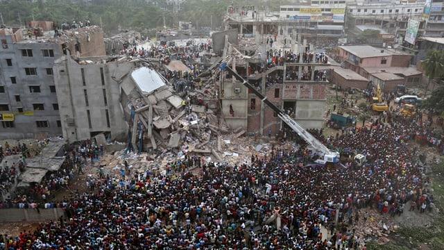 Menschenmasse vor dem eingestürzten Gebäude.