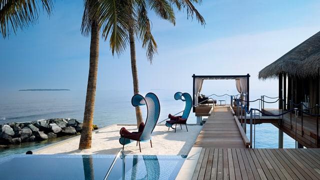 Ein Pool mit futuristische Liegestühlen und einem Bungalow mit Sicht aufs Meer.