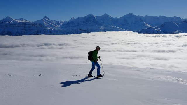 Ein Berggänger marschiert über das Schneefeld auf dem Burgfeldstand bei gleisendem Sonnenschein.