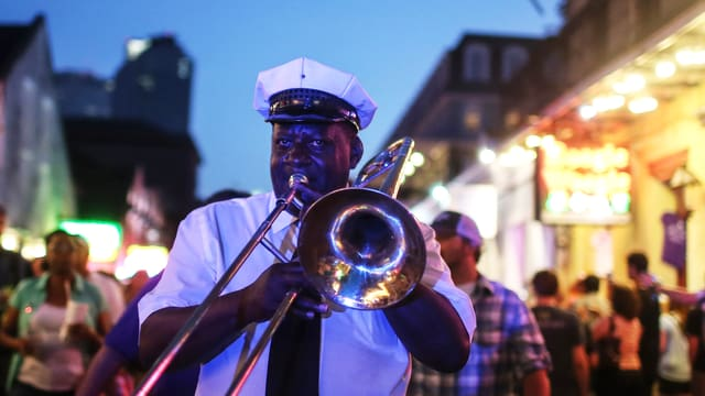 Ein Trompeter spielt in der Abenddämmerung im Gehen auf einer Strasse, umgeben von zahlreichen Menschen.