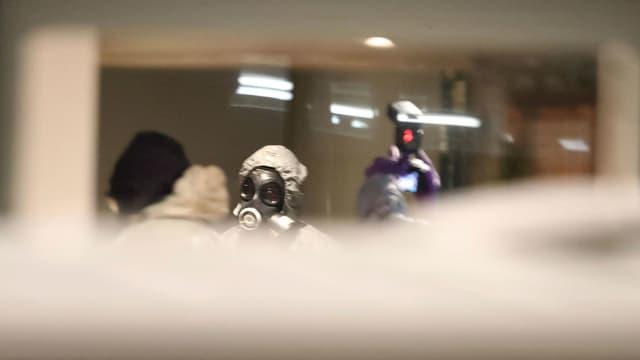 Männer mit Gasmasken untersuchen den Tatort.