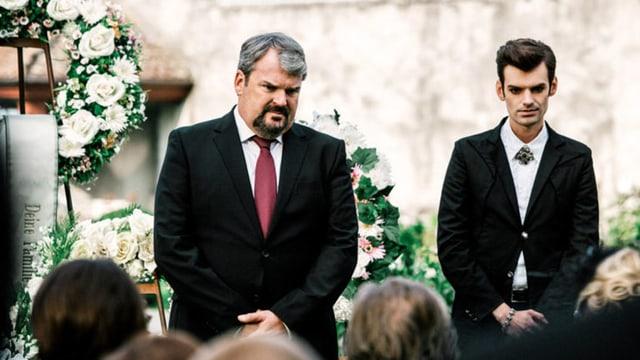 Luc Conrad und Fabio Testi aus der Serie «Der Bestatter» sind anwesend an einer Beerdigung. Im Hintergrund sieht man Blumenkränze, im Vordergrund weitere Anwesende.