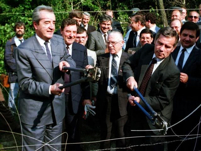 Zwei Politiker in Anzug mit grossen Stahlscheren