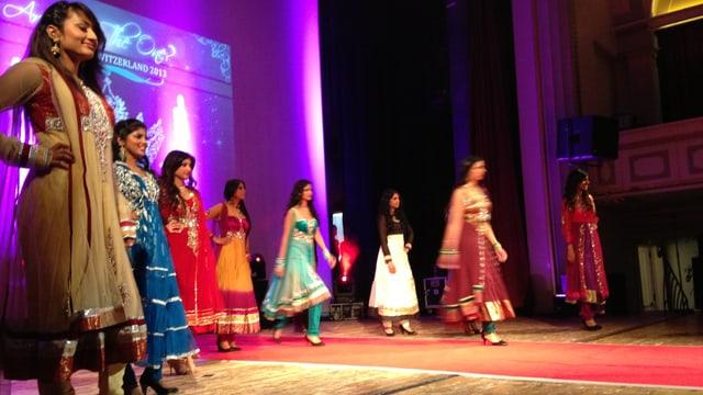 Acht tamilische Frauen in traditionellen, farbigen Gewändern auf einer Bühne.