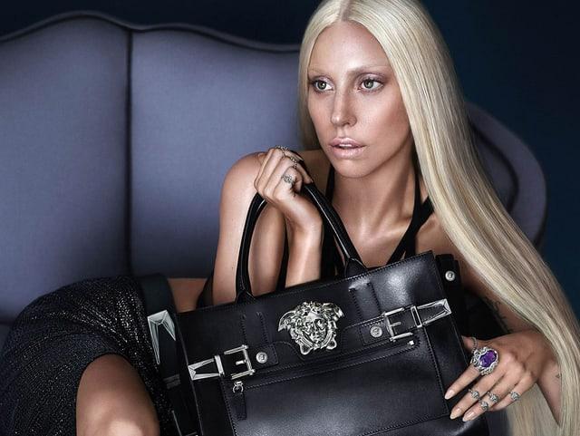 Lady Gaga posiert mit einer Handtasche.