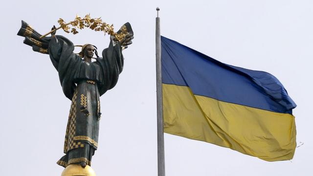 Das Unabhängigkeitsdenkmal sowie die Flagge der Ukraine in Kiew
