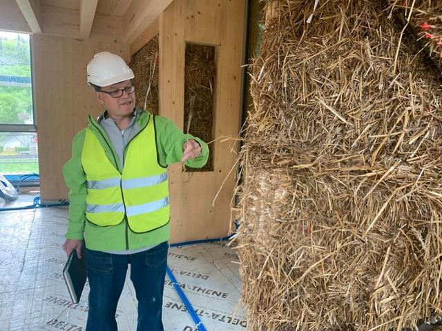 Bauleiter Uwe Jakob erklärt, wie gut Stroh isoliert.
