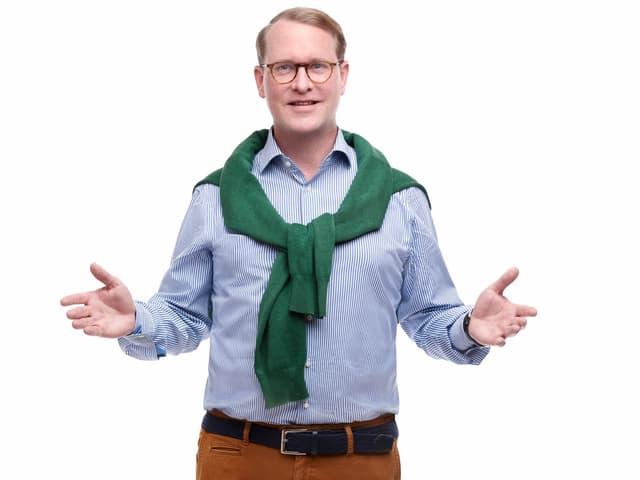 Hanspeter Vochezer im Streifenhemd, Pullover über der Schulter und braun-roter Hose