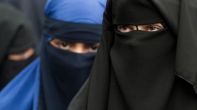 Zwei Frauen in voller Verschleierung, die eine blau, die andere schwarz. Nur die Augen sind sichtbar.