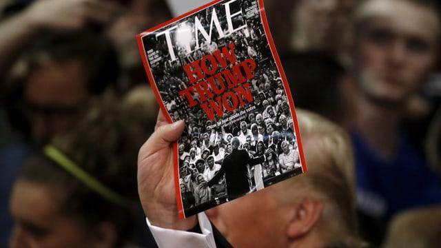 Trump hält Ausgabe von Time hoch.