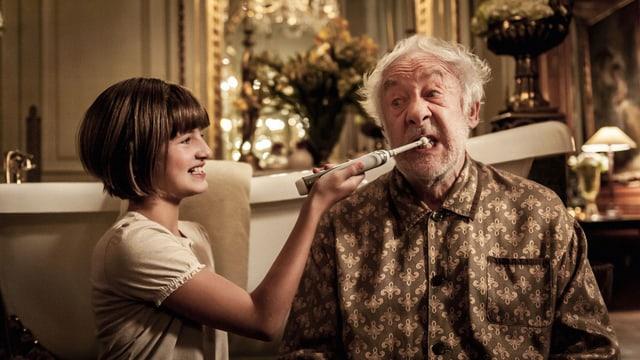 Ein Mädchen hilft einem ältern Mann beim Zähneputzen mit einer elektrischen Zahnbürste.