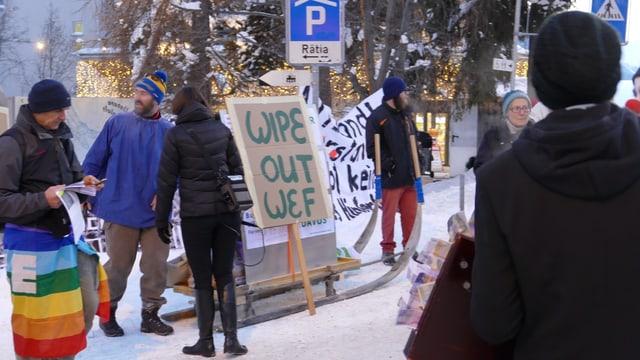 """Ein paar Personen stehen rund um ein Plakat mit der Aufschrift """"Wipe Out WEF""""."""
