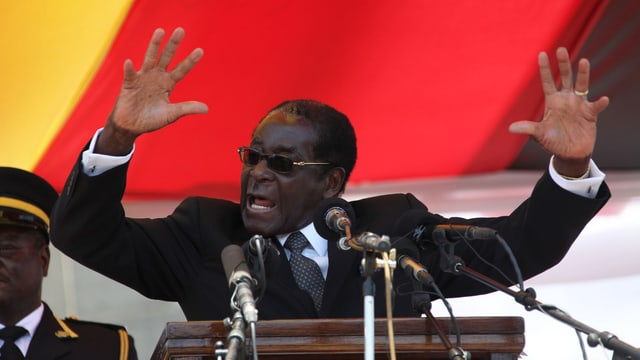 Mugabe an einem Rednerpult, hinter ihm eine Flagge.
