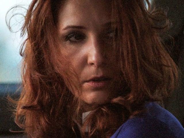 Eine Frau blickt erstaunt. Sie hat rotes, unruhiges Haar.