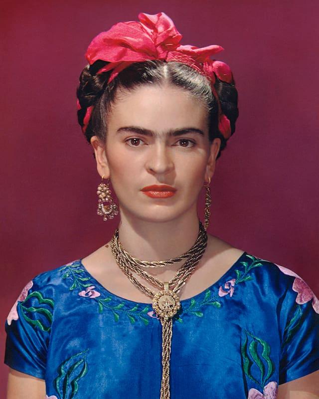 Frau mittleren Alters auffälligem Hals- und Ohrenschmuck, roter Schleife im Haar und ernstem Blick.
