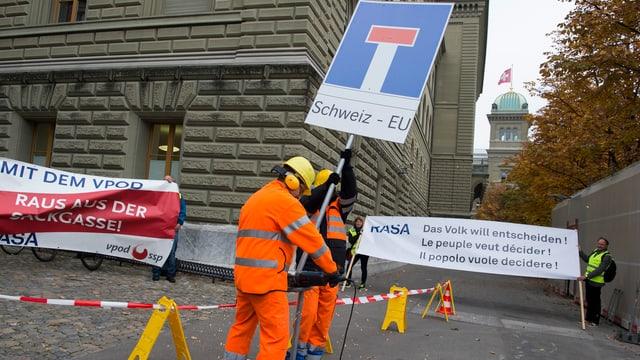 Die Initianten der Rasa-Initiative mit Schildern und in Bauarbeiter-Kleidung.