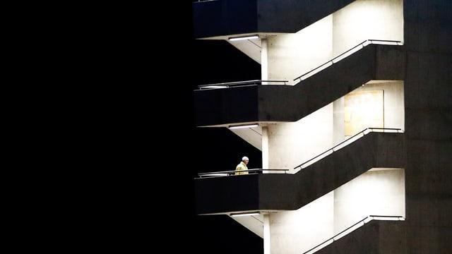 Ein Mensch auf einem beleuchteten Treppenhaus in der Dunkelheit.
