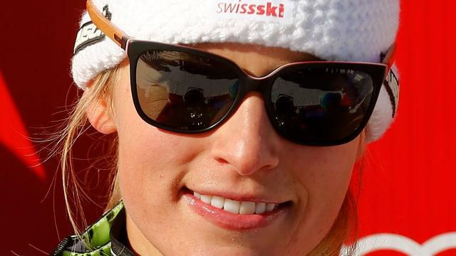 La skiunza Lara Gut cun egliers da sulegl gronds e chapitscha da Swissski.