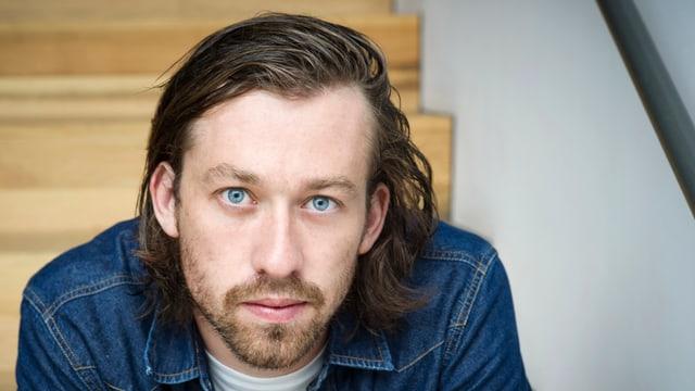 Mann mit blauen Augen und langem blondem Haar