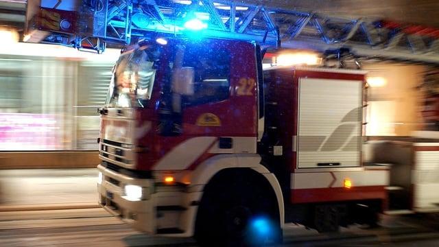 Ein Feuerwehrauto ist mit Blaulicht unterwegs