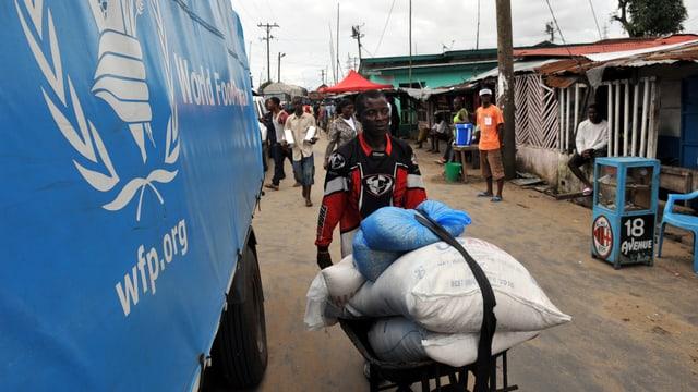 Ein Mann transportiert mit einer Schubkarre Säcke voller Lebensmittel, im Bild auch ein Lastwagen des World Food Program.
