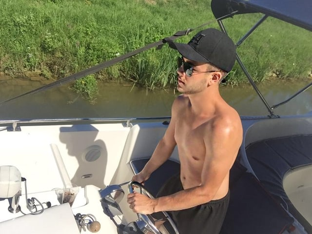 Luca Hänni mit nacktem Oberkörper am Steuer des Bootes.