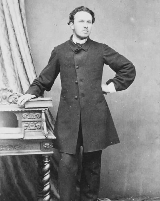 Ein junger Mann posiert adrett gekleidet.