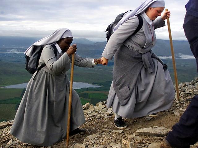 Zwei Nonnen in hellgrauen Gewändern und ausgerüstet mit Holzstock und Turnschuhen gehen Hand-in-Hand auf einem schmalen Pfad.