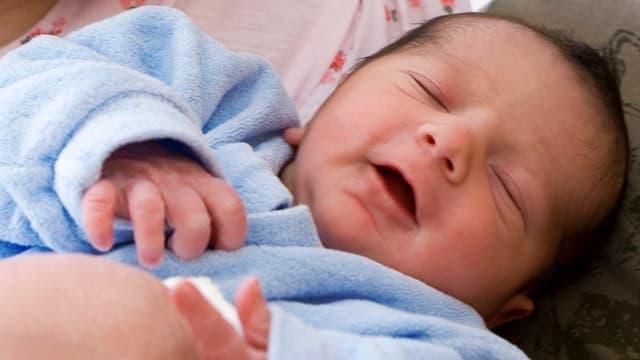 Baby mit schwarzen Haaren und blauem Strampler