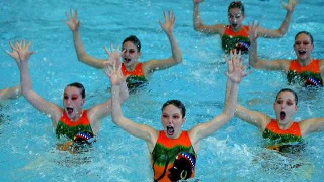 Fünf Synchronschwimmerinen stehen im Wasser und halten ihre Arme hoch.