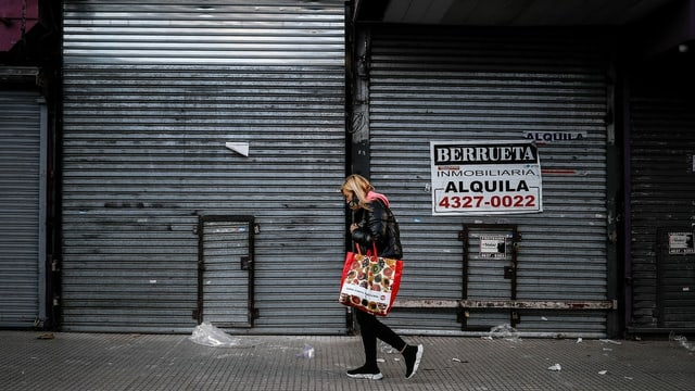 Eine Frau läuft an einem geschlossenen Geschäft vorüber