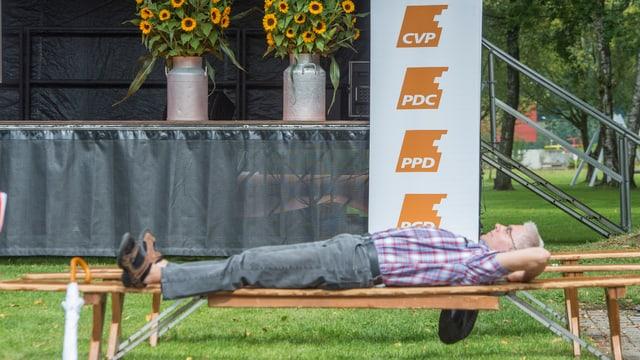 Eine Person ruht sich auf einer Festbank vor einem CVP-Logo aus.