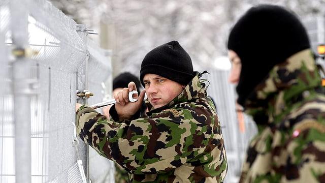 Soldaten der Schweizer Armee errichten eine Abzäunung.