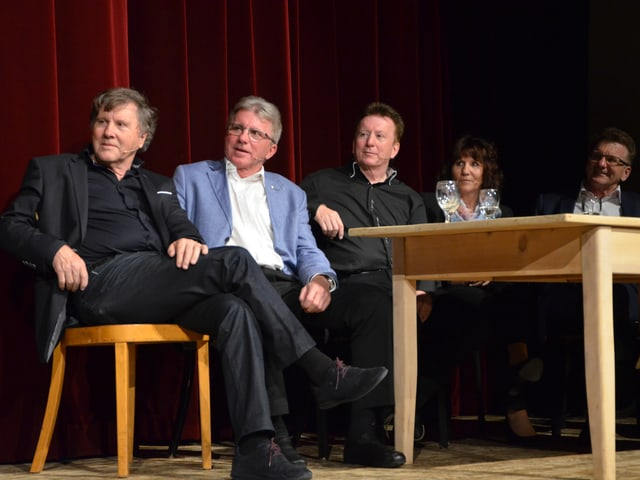 Fünf Personen sitzen an einem Tisch.
