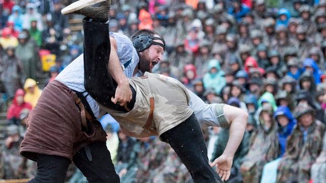 Zwei Schwinger beim Kämpfen in einer Arena vor viel Publikum.