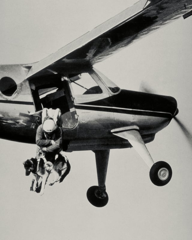 Rettungshelfer springt mit Hund aus Kleinflugzeug.