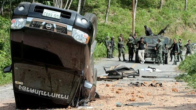 Umgekehrtes Auto und Soldaten auf Strasse.