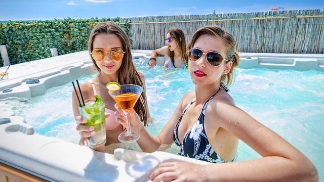 Zwei junge Frauen im Whirlpool mit Cocktail in der Hand