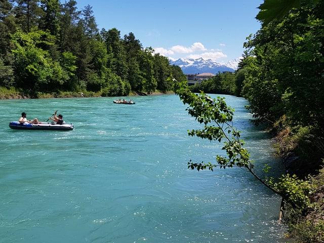 Mehrere Schlauchboote im Fluss. Am Ufer hat es viele Bäume und am Himmel befinden sich nur wenige Wolken.