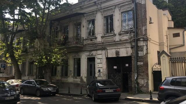 Eine verwittertes Haus in Tiflis, vor dem teure Autos parken.