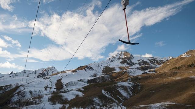 Ein Skilift, dahinter Berge mit wenig Schnee