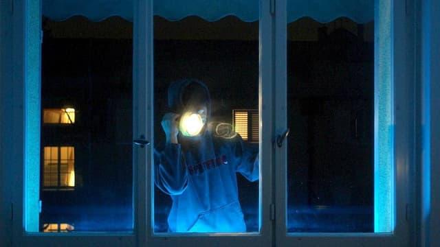 Mann leuchtet in der Nacht mit Taschenlampe in Haus.