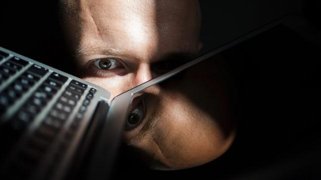 Mann starrt aus dem Dunkeln mit einem Auge auf einen Laptop. Der Bildschirm spiegelt seinen Kopf wider.