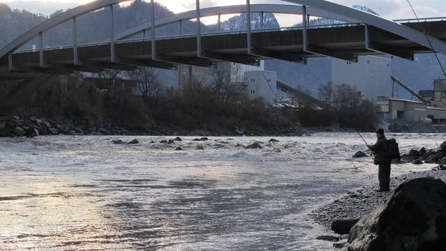 Ein Fischer steht am Rhein und wartet auf einen Biss
