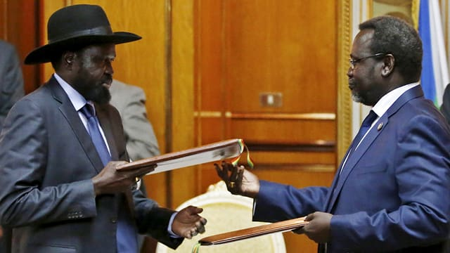 Zwei Politiker tauschen Dossiers aus.