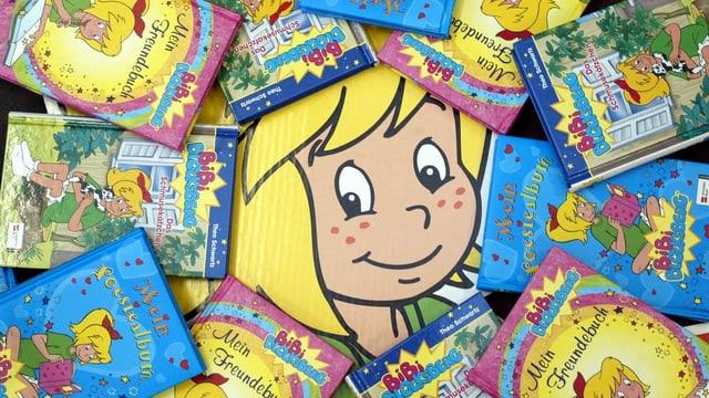 Kleines blondes Mädchen grinst inmitten von Büchern hervor