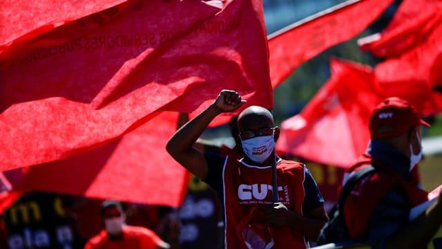 Demonstrierende in roten Shirts vor einer roten Fahne.