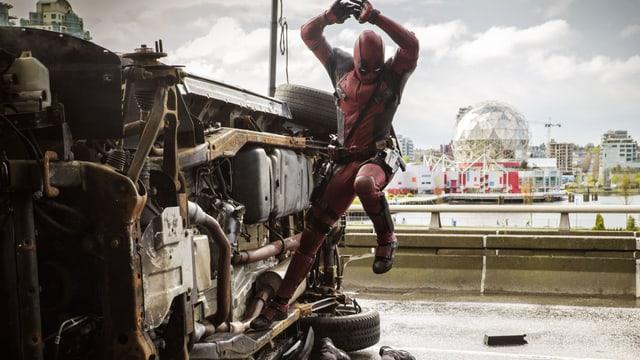 Deadpool in der Luft neben Auto, das auf der Seite liegt.