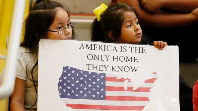Zwei Mädchen mit Schild, darauf steht: Amerika ist die einzige Heimat, die sie kennen.